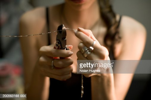 Female jeweller cutting chain with pincers, close-up : Stock Photo