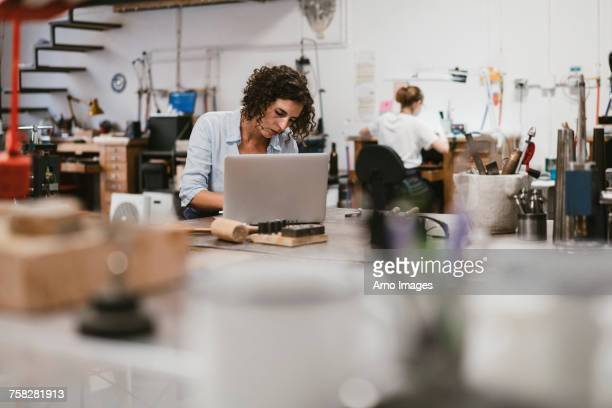 Female jeweller typing on laptop at workbench