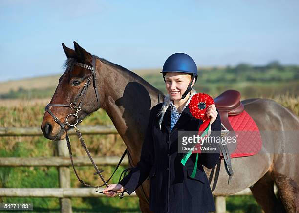 Female jockey and horse with winning rosette.