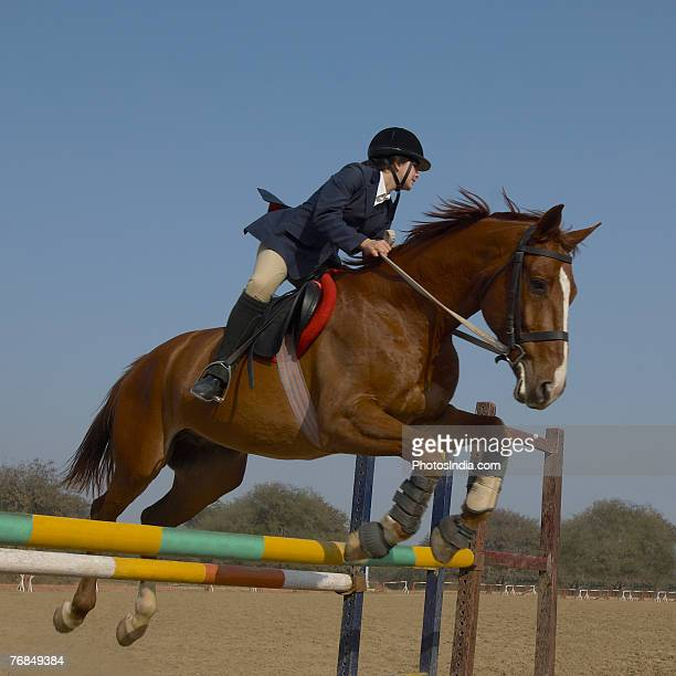 Female jockey riding a horse and jumping over the hurdle