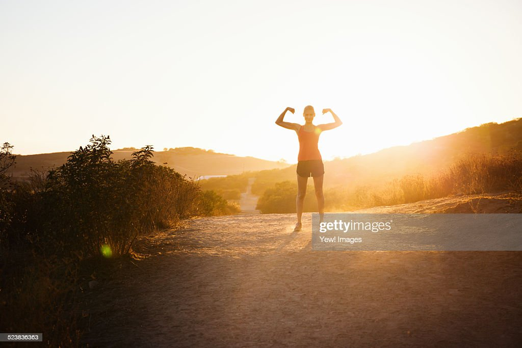 Female jogger flexing arms in sunlight, Poway, CA, USA