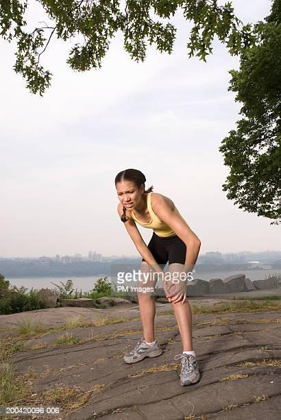 Female jogger holding knee