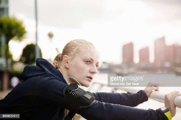 Female jogger looks out over city, while stretching legs.