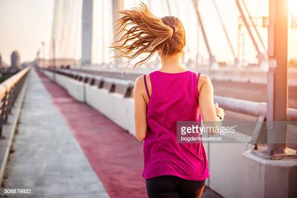 Mujer corriendo en el puente impulsor
