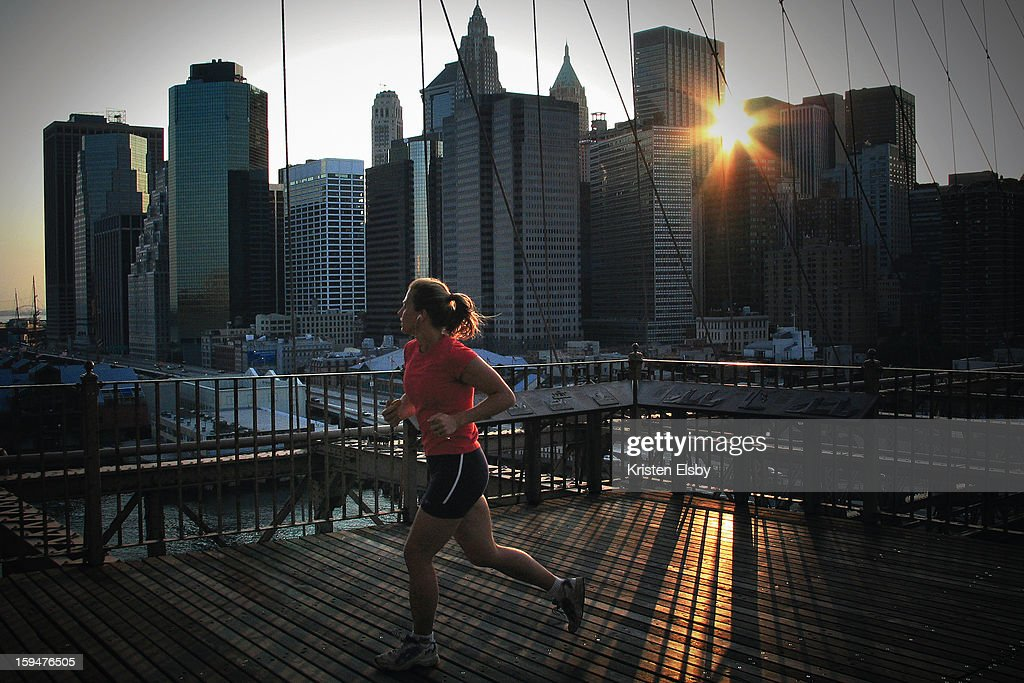 CONTENT] A female jogger runs across Brooklyn Bridge during sunset on a summer evening in New York City.