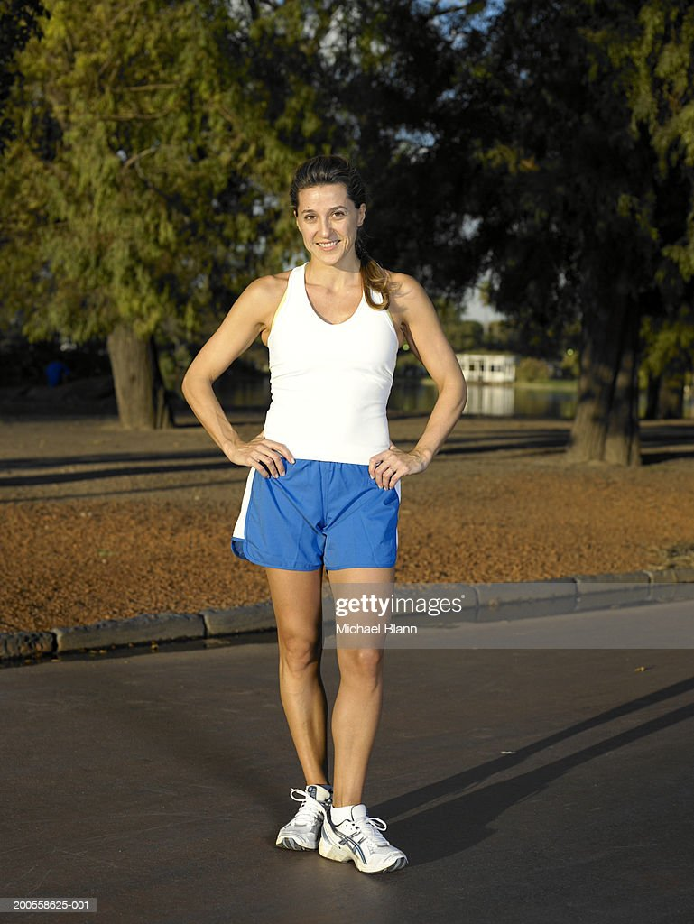 Female jogger standing in park, arms akimbo, portrait : Stock Photo