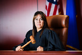 Female judge sitting in court holding her gavel