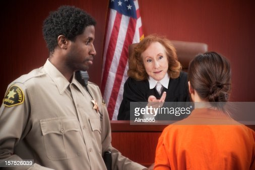 Female judge talking to a prisoner with court officer watching