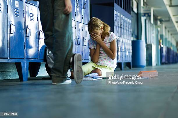 Female junior high student sitting on floor holding head in hands, boy standing smugly nearby