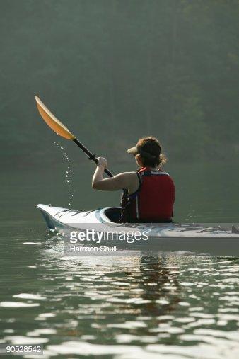 Female kayaker on a lake.