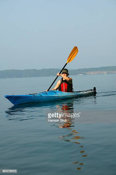 Female kayaker on a lake.