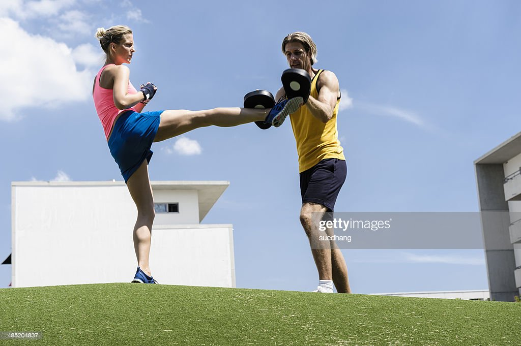 Female kick boxer and personal trainer in park