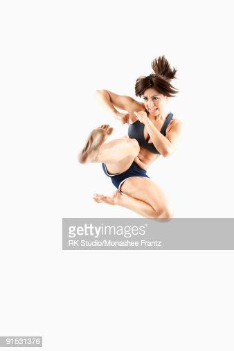 Female Kickboxer doing a 'High Jump Leg Punch'. : Stock Photo