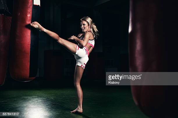 Female kickboxer fighter training with a punching bag