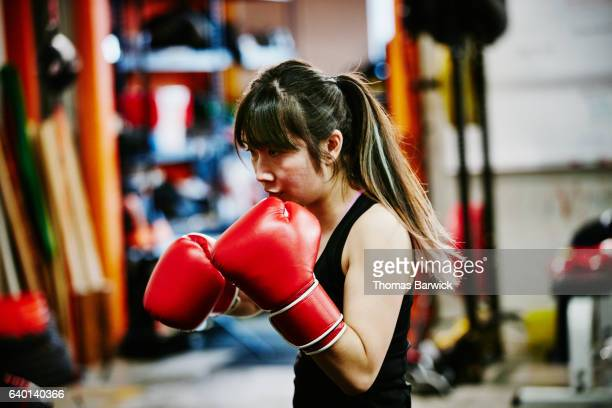 Female kickboxer working out in fighting gym