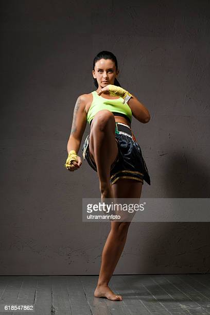 Female kickboxing   Athletic woman fighter kicking Sports training