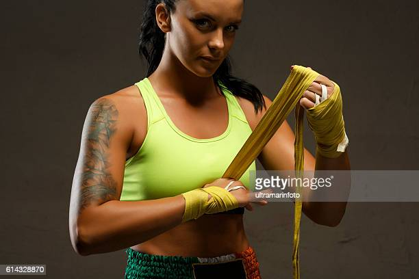 Female kickboxing   Athletic woman wrapping hands with yellow boxing wraps