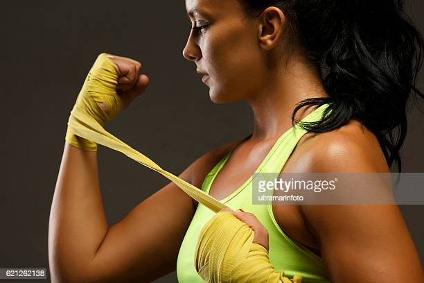 Athletic mujer de kickboxing Hembra de envoltura manos con envolturas de boxeo amarillo