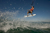 Female kiteboarder mid-air, holding line one handed, low angle view