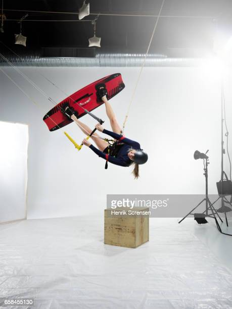 Female kitesurfer inverted in a studio