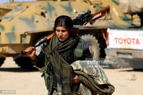 TOPSHOT A female Kurdish fighter of the USbacked Syrian Democratic Forces made up of an alliance of Arab and Kurdish fighters walks carrying a weapon...