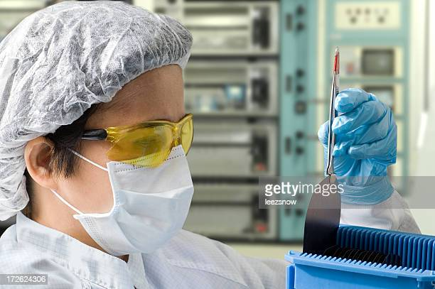Female Lab Technician Inspecting A Silicon Wafer