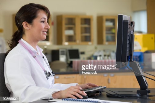 Female lab technician working on a computer : Stock-Foto