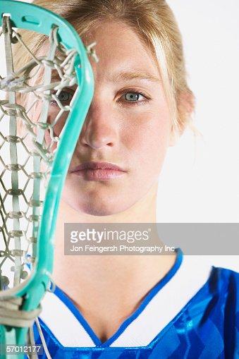 Female lacrosse player holding lacrosse stick