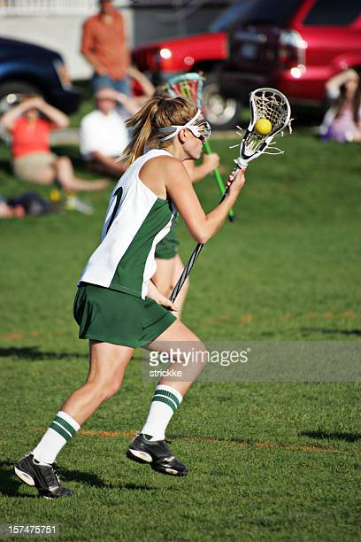 Female Lacrosse Player in Green and White Runs with Ball
