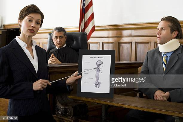 Female lawyer pointing at an exhibit in front of a judge and a victim