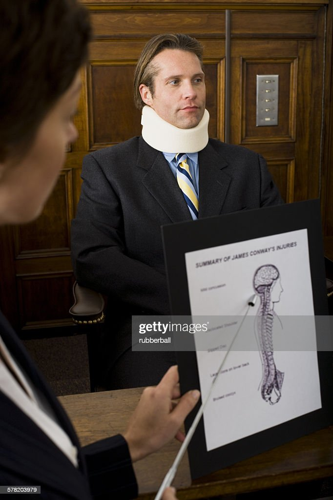 A female lawyer pointing at evidence in front of a victim in a courtroom : Stock Photo