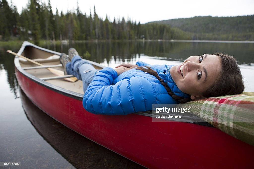 A female laying in a canoe. : Stock Photo