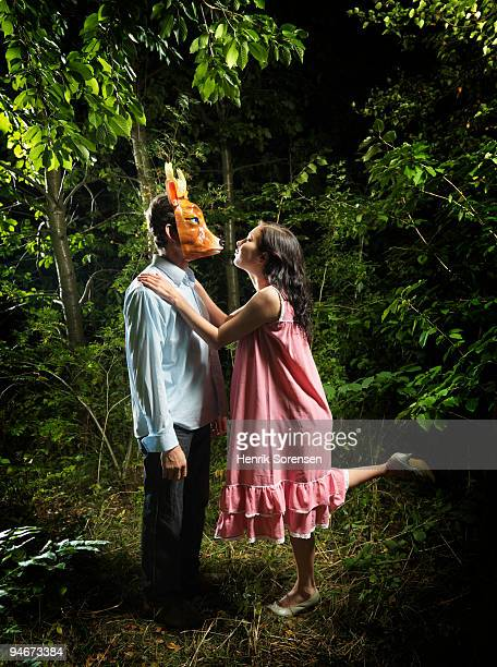 Female leaning to kiss male in reindeer mask