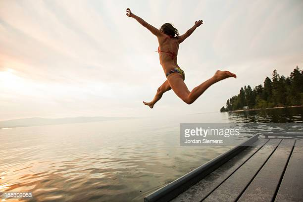 A female leaps into the cool water of a lake.
