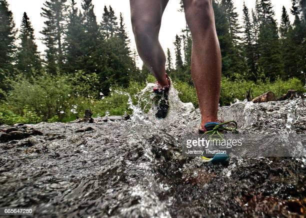 Female legs and feet running and splashing through water