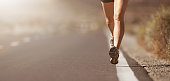 Female legs close up of a woman running on a road with sports shoes
