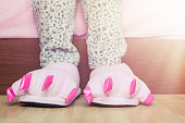 Female legs in warm pajama and cute pink monster foot slippers with big claws on parquet floor near a bed in bedroom. Bedtime and good morning concept.
