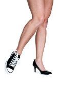 Female legs wearing a sneaker and high heel shoe
