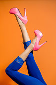 Female legs wearing high heels over bright background