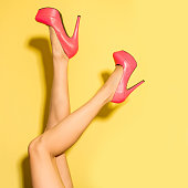Female legs wearing high heels isolated over yellow background