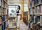 Female librarian returning books to shelves in library