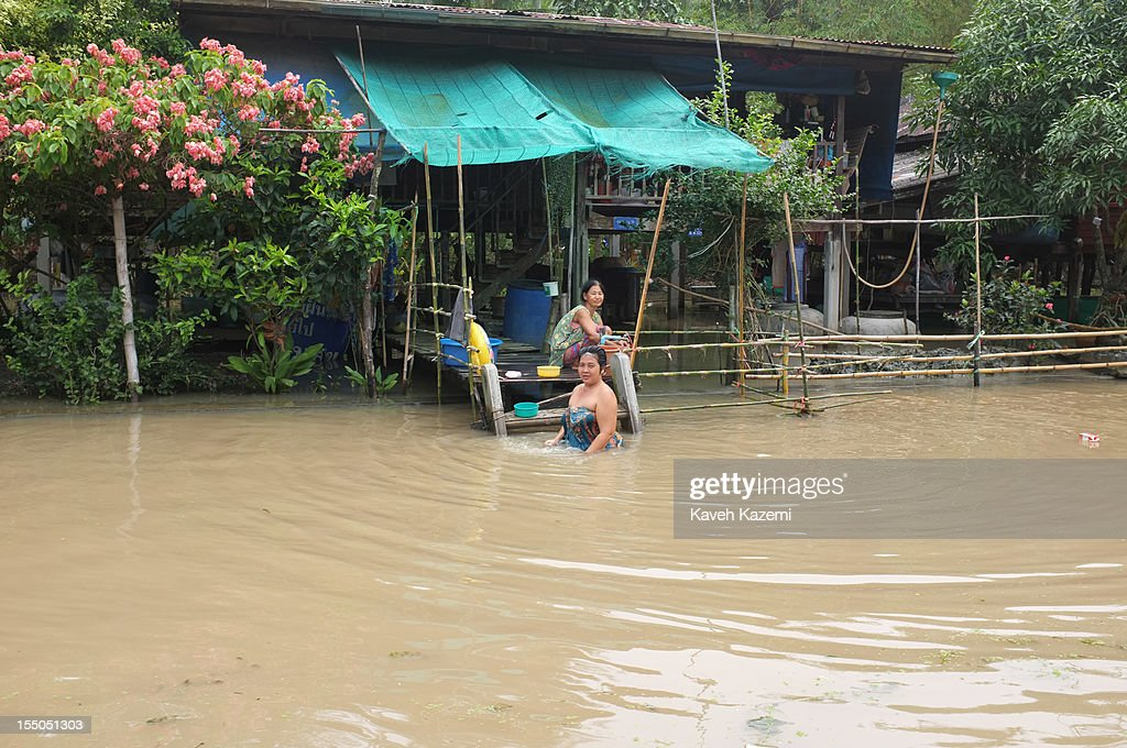 A female local resident bathes in the water outside her home located in the heart of canals near floating market on October 13 in Damnoen Saduak, Thailand. Damnoen Saduak is a district in the province of Ratchaburi in central Thailand. The central town has become a tourist attraction with its famous floating market.