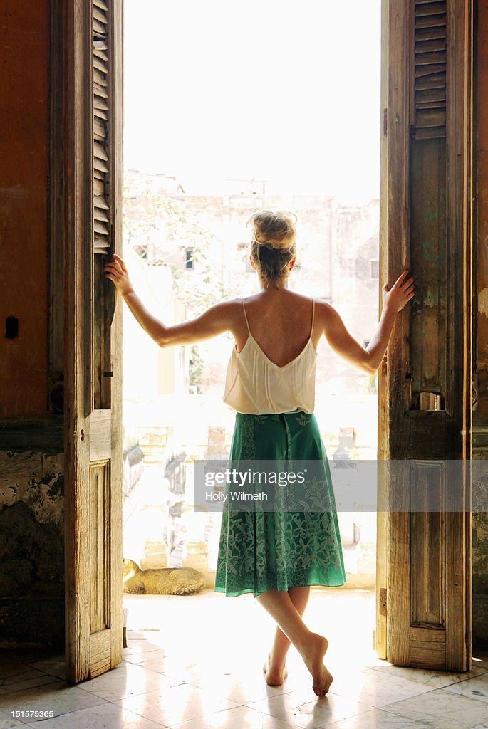 Female looking out veranda in Havana, Cuba. : Stock Photo