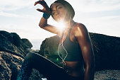 Fitness female looking tired after intense physical training with sun flare. Woman standing by the rocks at the beach with hand on head.