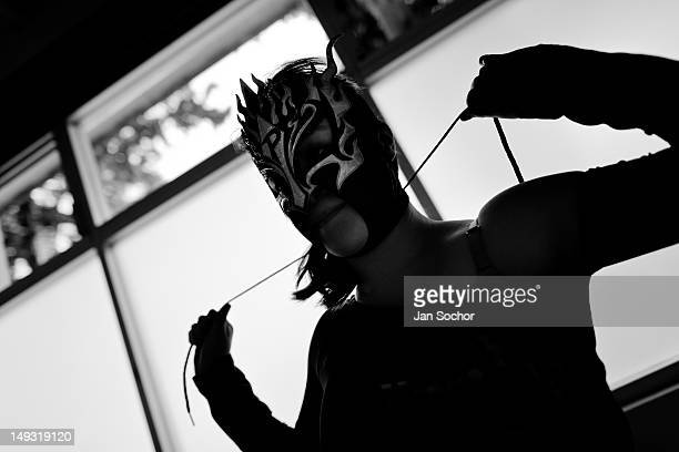 A female Lucha libre wrestler Sexy Polvora ties up her mask before a fight at a local arena on April 29 2012 in Mexico City Mexico Lucha libre...