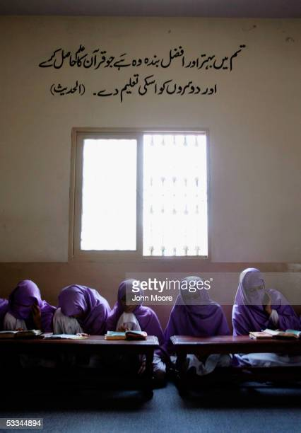 Female madrassa students their heads covered in Islamic tradition study the Koran during class on August 4 2005 in Multan Pakistan The writing in...