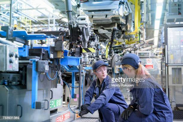 Female maintenance engineers working on production line in car factory