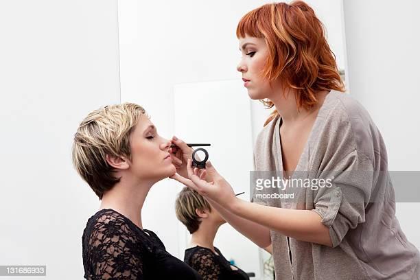 Female makeup artist applying eye shadow to model
