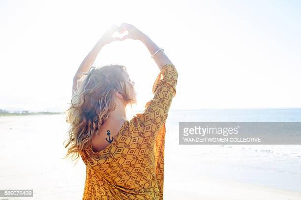 Female making heart shape around the sun flare