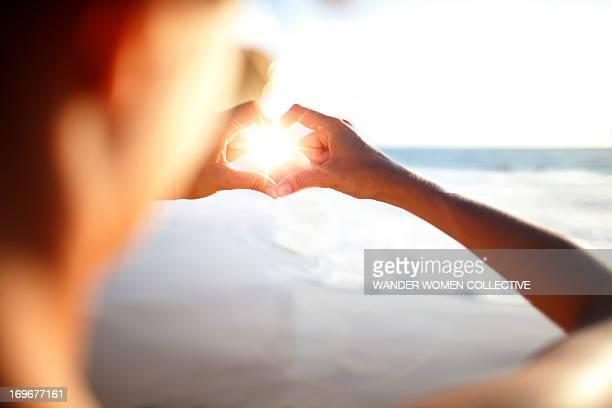 Female making heart shape with hand sun flare